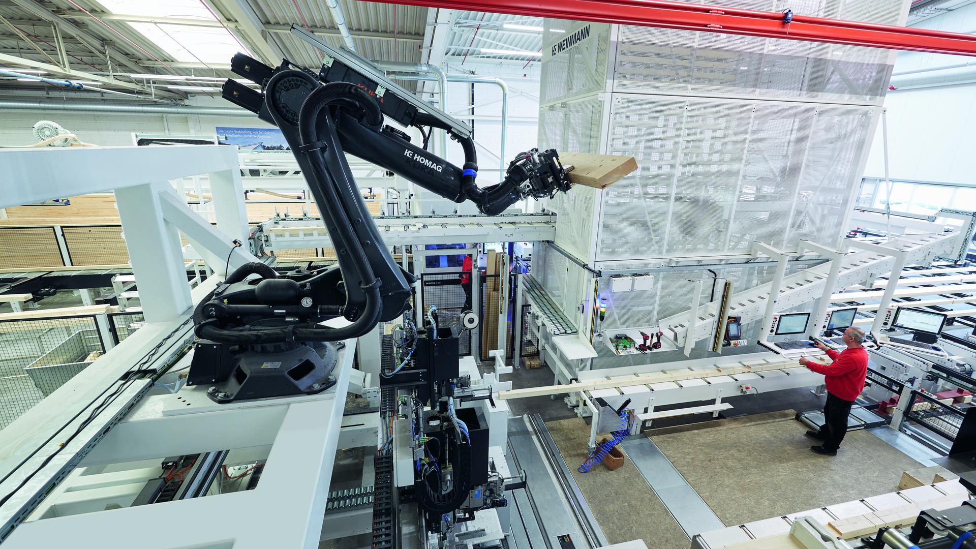 """Ein Roboter setzt bei """"WeberHaus"""" in Rheinau-Linx Rahmen für Fertigteilhäuser zusammen."""