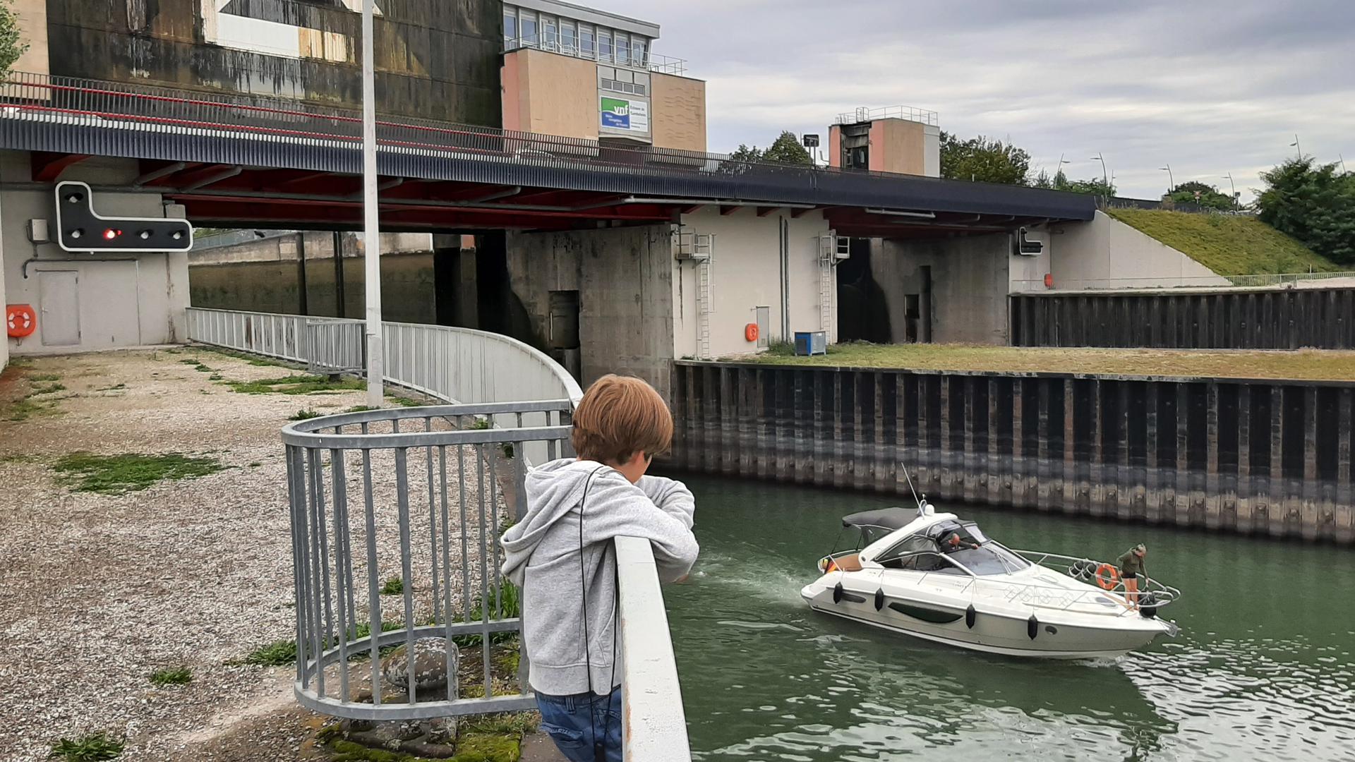Junge steht am Rhein und beobachtet, wie ein Schiff aus der Schleuse fährt.