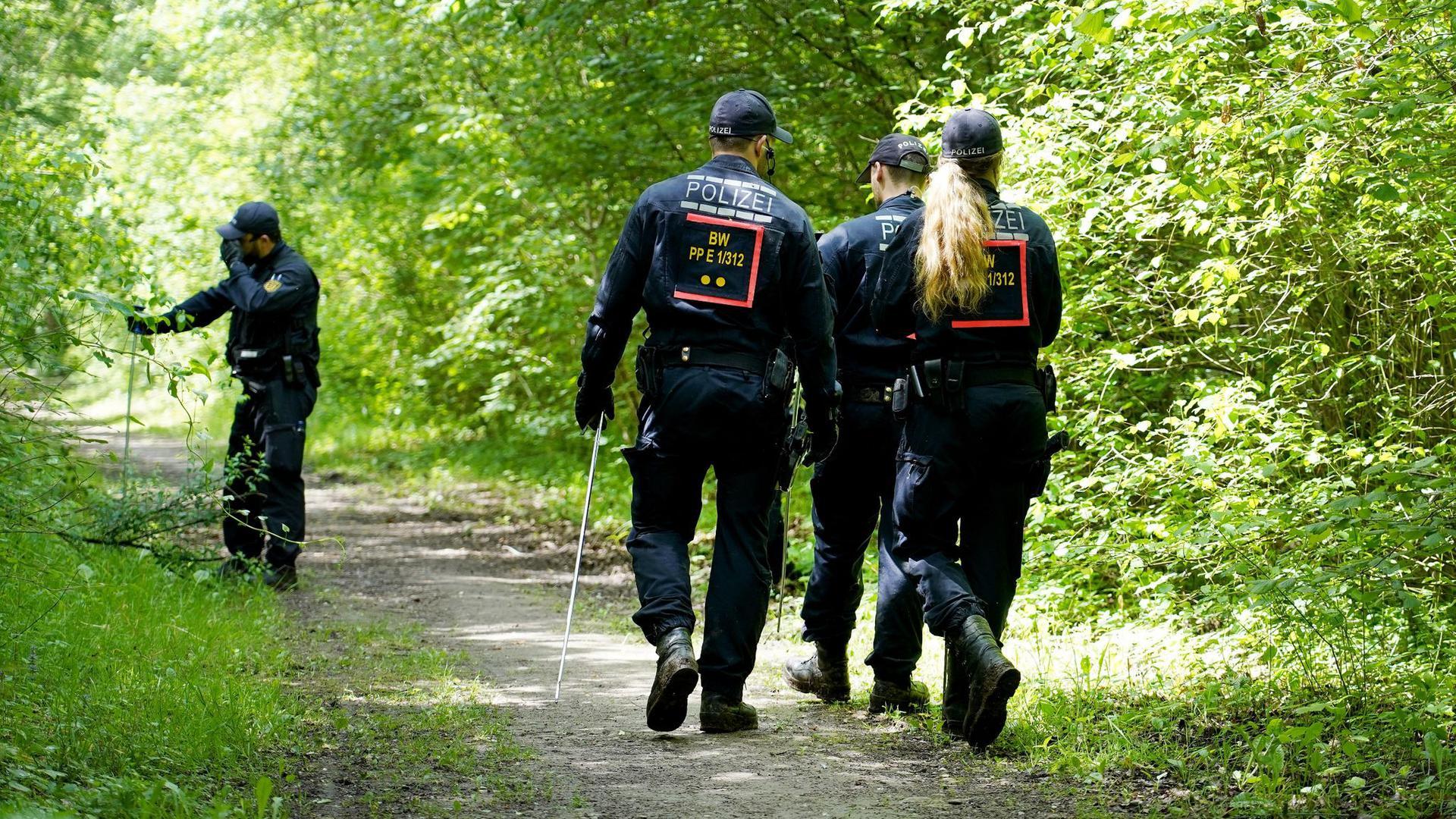Polizeibeamte suchen in der Umgebung des Fundorts derLeiche der Artistin nach Spuren.
