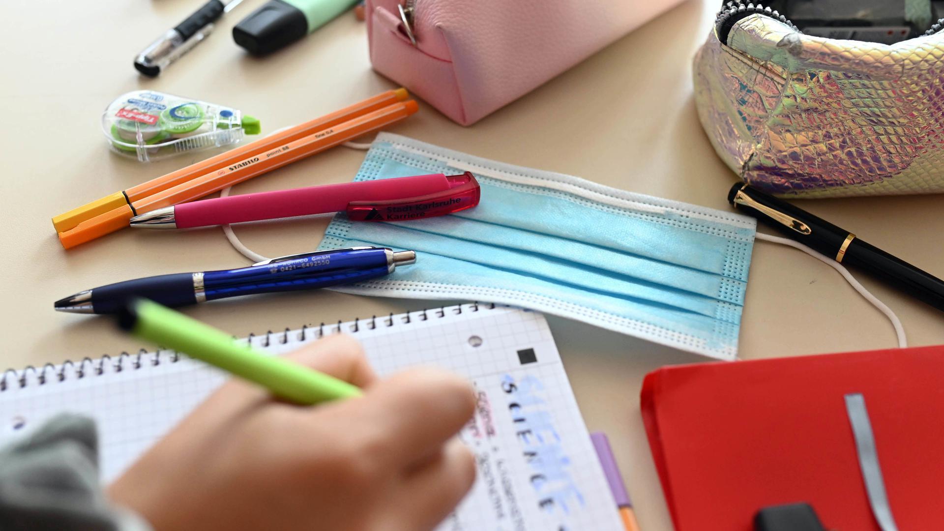 Während einer Unterrichtsstunde einer zehnten Klasse liegt ein Mund-Nasen-Schutz auf dem Tisch einer Schülerin.