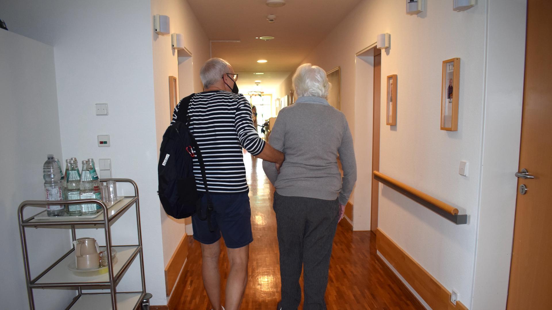 Ein Mann mit Rucksack über der Schulter geht mit einer weißhaarigen Frau Arm in Arm über einen langen Flur.