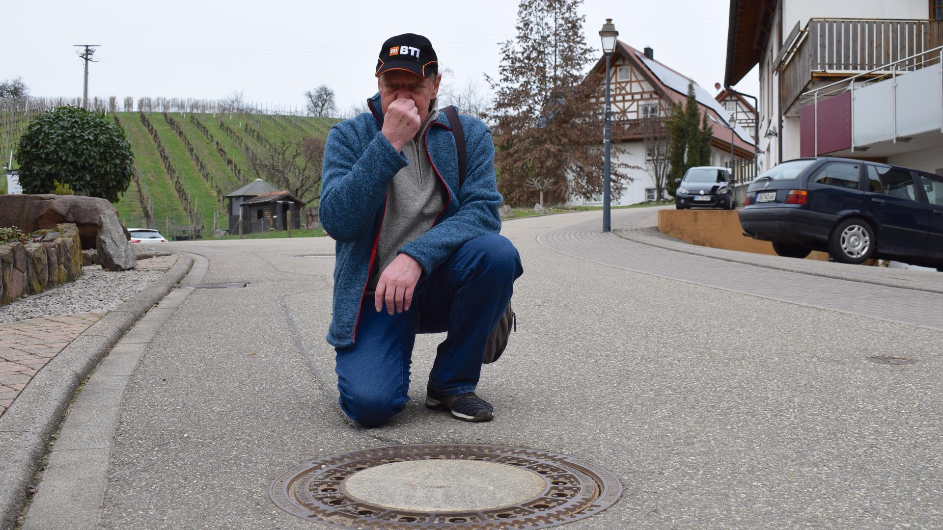 Ein Mann kniet an einem Kanaldeckel und hält sich die Nase zu.