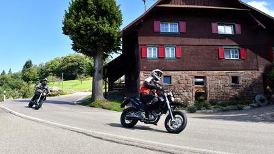 Zwei Motorradfahrer fahren in einer Kurve an einem Haus vorbei.