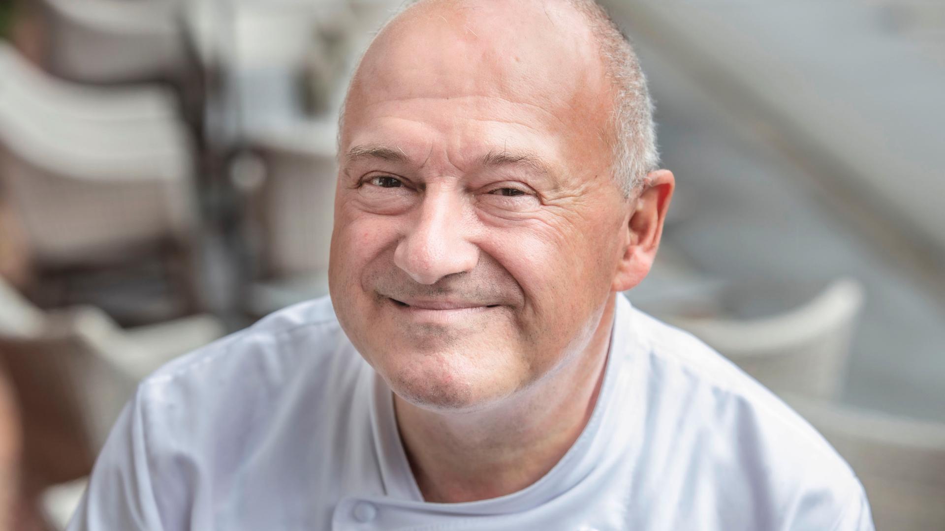 Mann mit wenigen grauen Haaren, der lächelt
