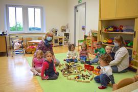 Eine Gruppe Kleinkinder und zwei Erzieherinnen sitzen auf dem Boden im Rathaus in Sasbachwalden.