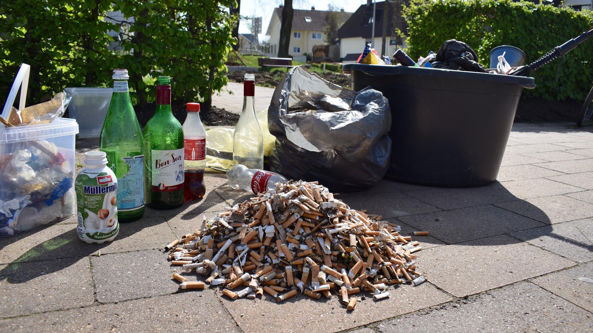 Ein Berg Zigarettenkippen und leere Flaschen.