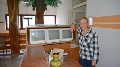 Ein Frau mit Brille steht hinter einem Tresen, an dem alte Bildschirme stehen. Im Hintergrund sind eine künstliche Palme und ein alter Kleiderständer zu sehen.