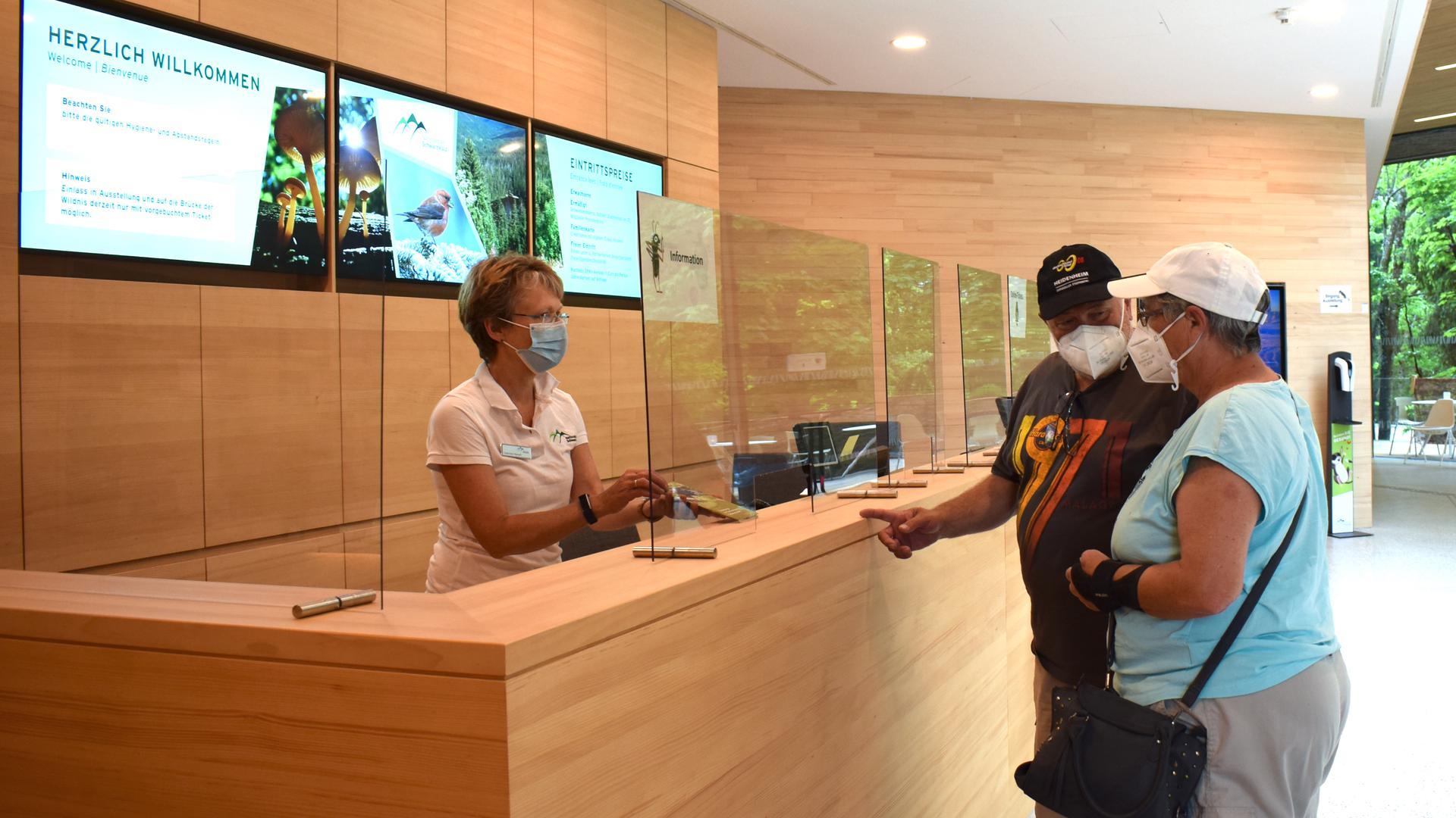 Zwei Besucher stehen im Kassenbereich des Gebäude des Nationalparkzentrum Schwarzwald.