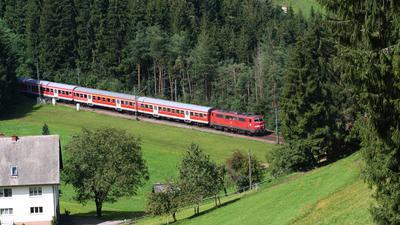 Eine E-Lok der Baureihe 111 mit den klassischen Nahverkehrs-Wagen passiert auf der Schwarzwaldbahn den Unterhippensbachhof.