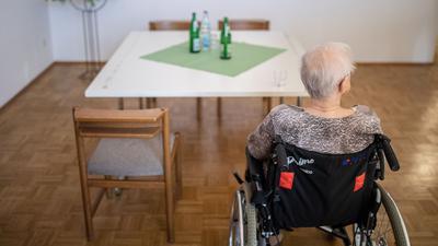 Eine Seniorin sitzt in einem Rollstuhl an einem Tisch.