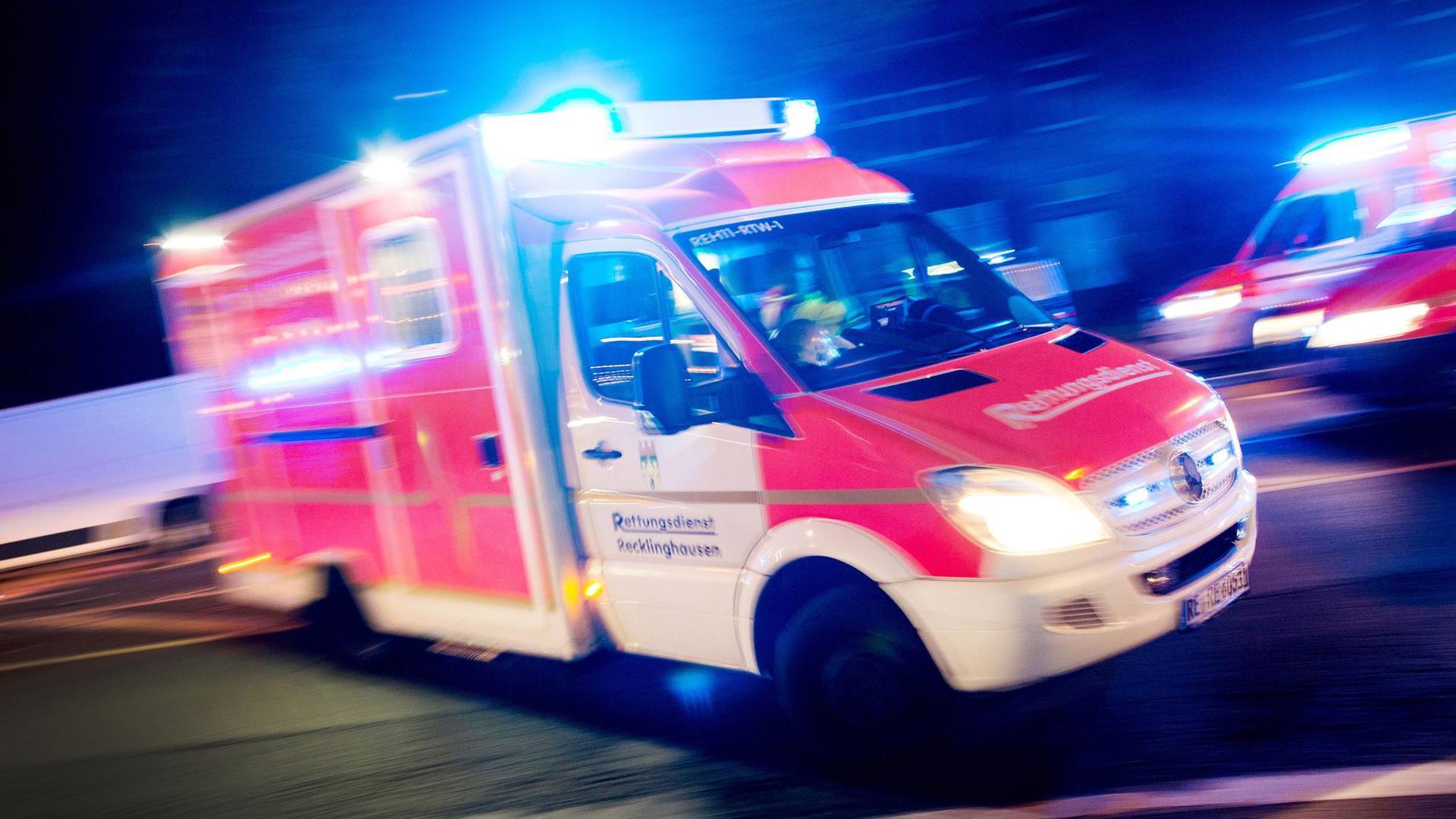 Ein Rettungswagen fährt mit Blaulicht über eine Straße.