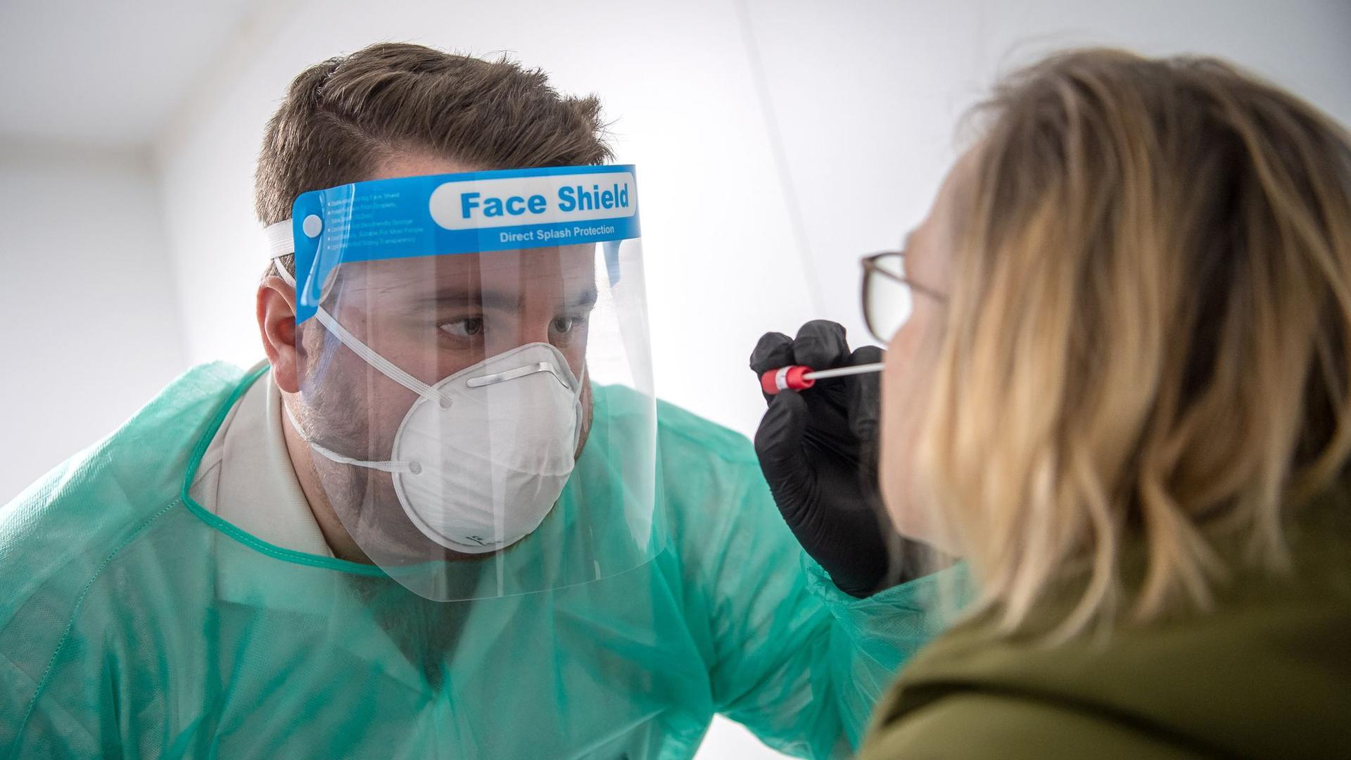 Ein Abstrich für einen PCR-Test wird von einem Mitarbeiter im Corona-Testzentrum genommen.