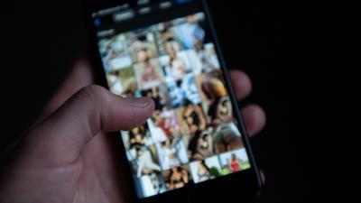 Ein Mann schaut sich auf einem Smartphone pornografische Bilder an.