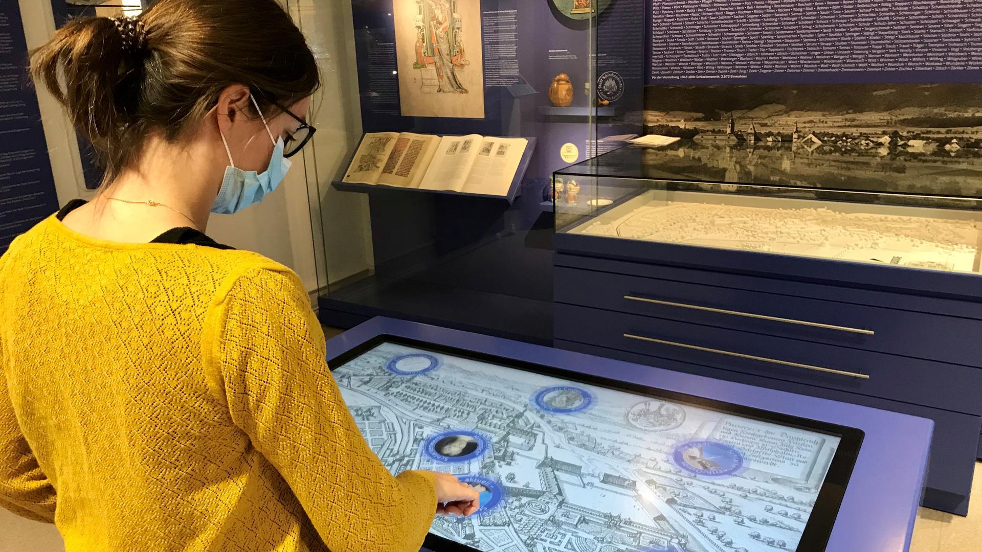 Eine junge Frau bedient einen großen Touchscreen.