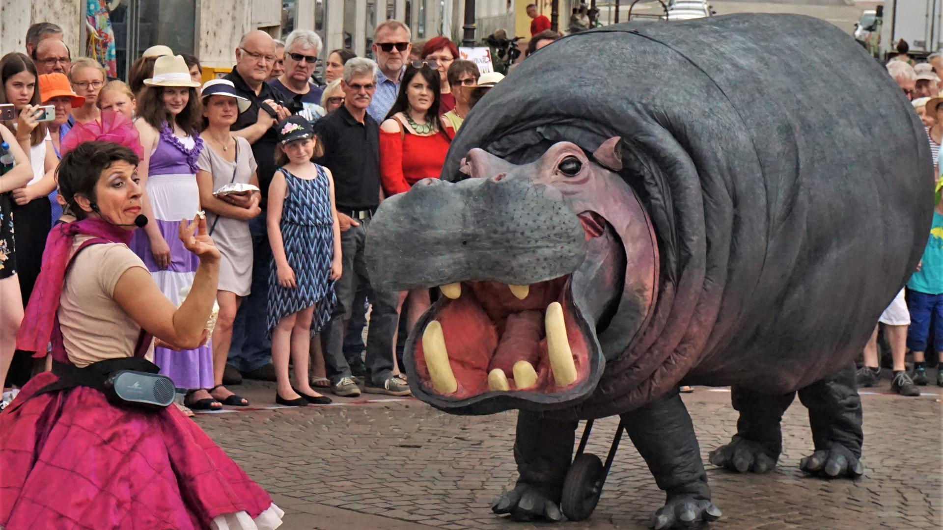Eine Menschenmenge beobachtet ein künstliches Nilpferd.