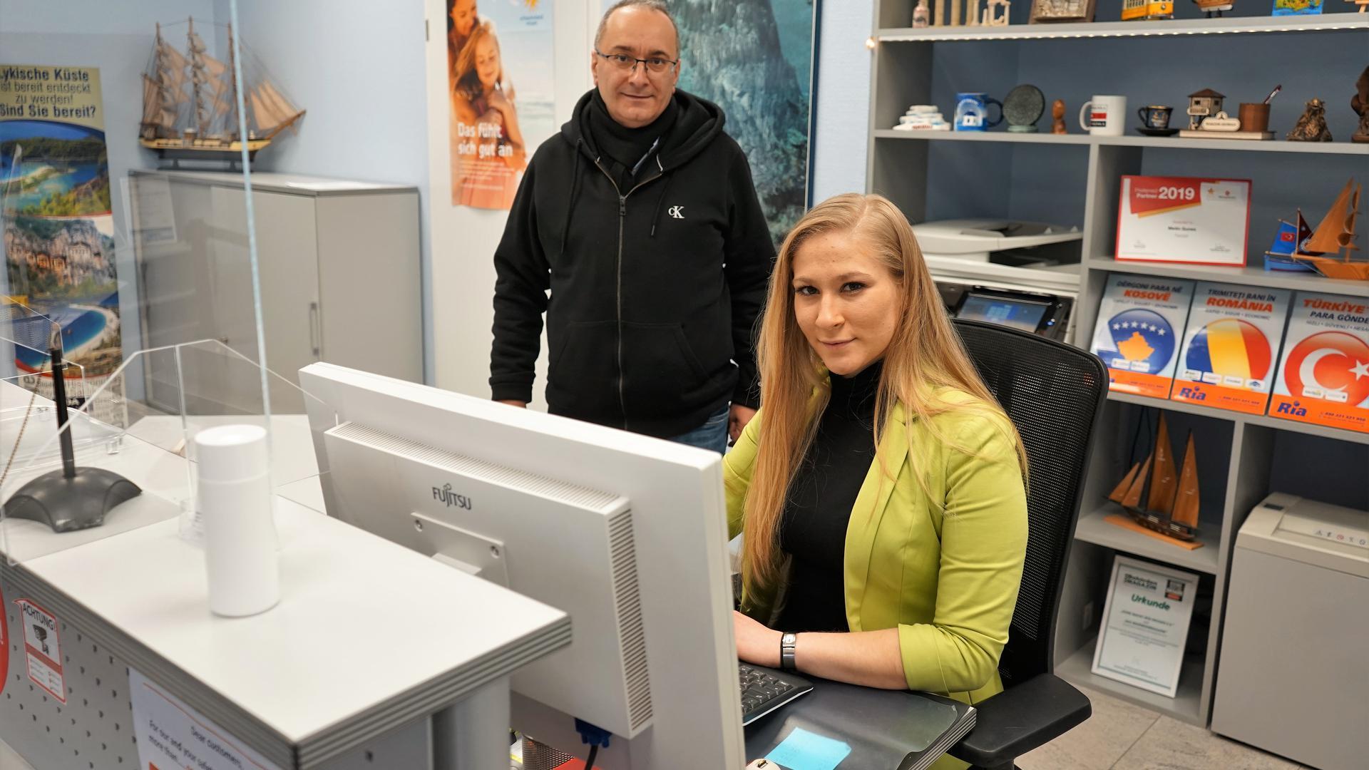 Ebru Karaagac sitzt im Reisebüro Günes an einem Rechner. Dahinter steht ihr Chef Metin Günes.
