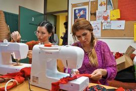Konzentriert bei der Arbeit: Frishta Amiri näht Rüschen, während Zohra Hassan (links) den gerissenen Faden wieder in die Nähmaschine einfädelt.