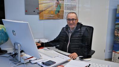 Reisebüro-Inhaber Metin Günes sitzt an seinem Arbeitsplatz.