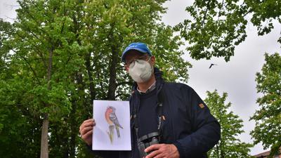 Ein Mann hält das Bild eines Vogels in der Hand