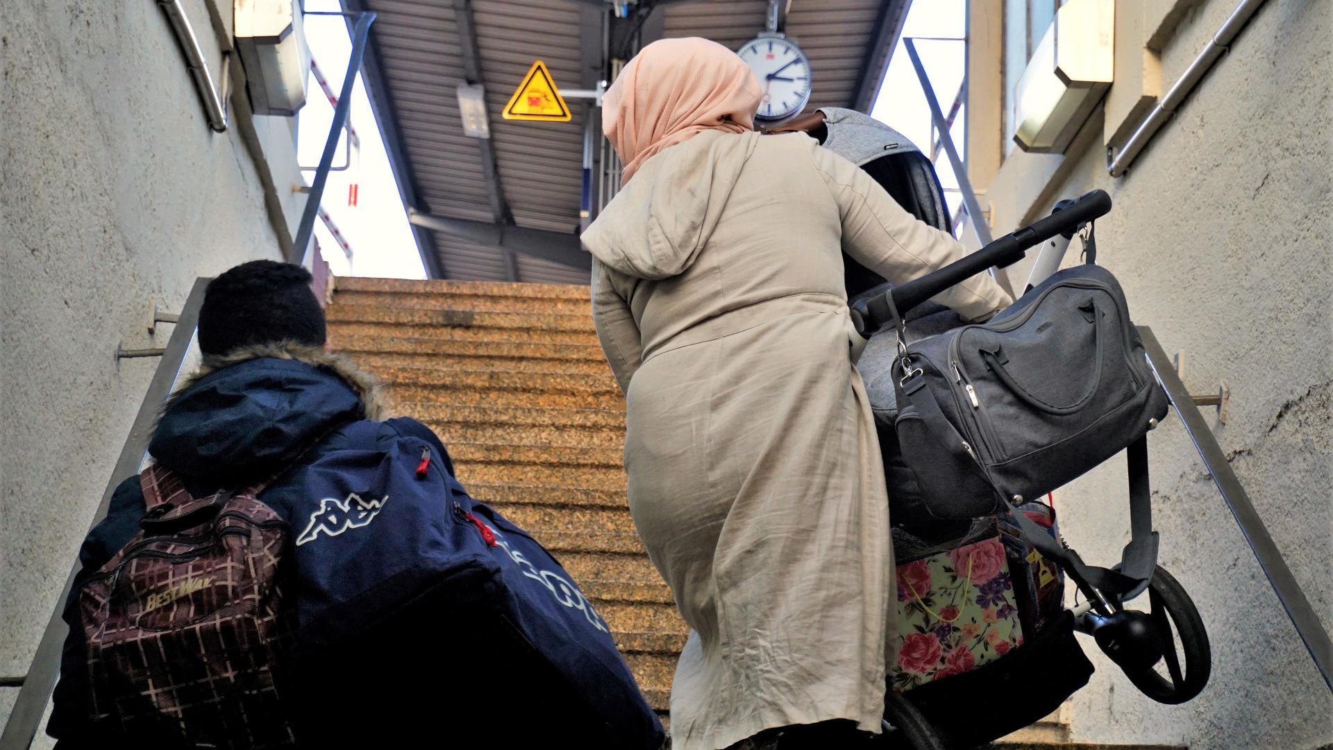 Eine Frau trägt einen Kinderwagen eine Treppe hoch.