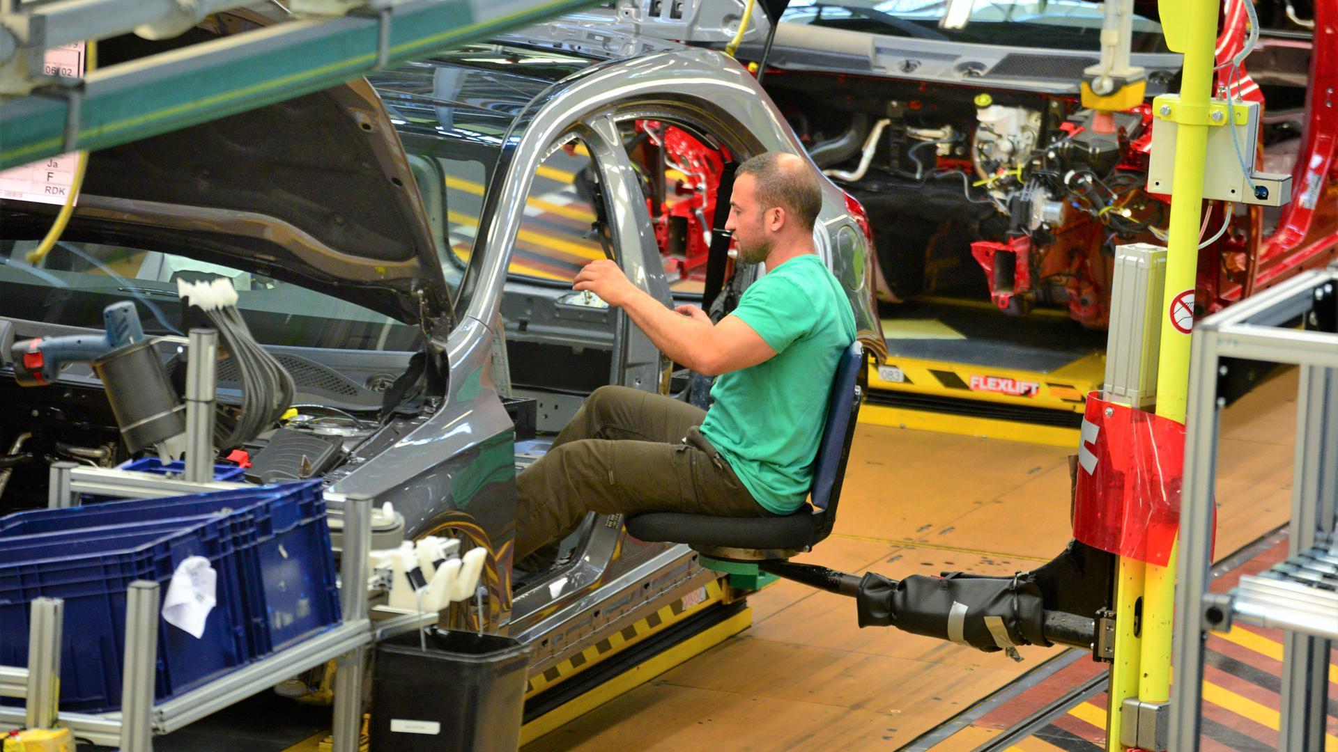 Ein Mann sitzt auf einem Stuhl an einem Fließband, auf dem Autos montiert werden.