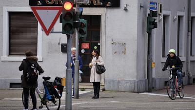 Fahrradfahrer und Fußgänger warten an einer Ampel in Rastatt.