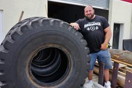 Strongman-Profi Dennis Kohlruss neben einem riesigen Autoreifen.