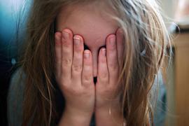Mädchen hält sich die Hände vors Gesicht.