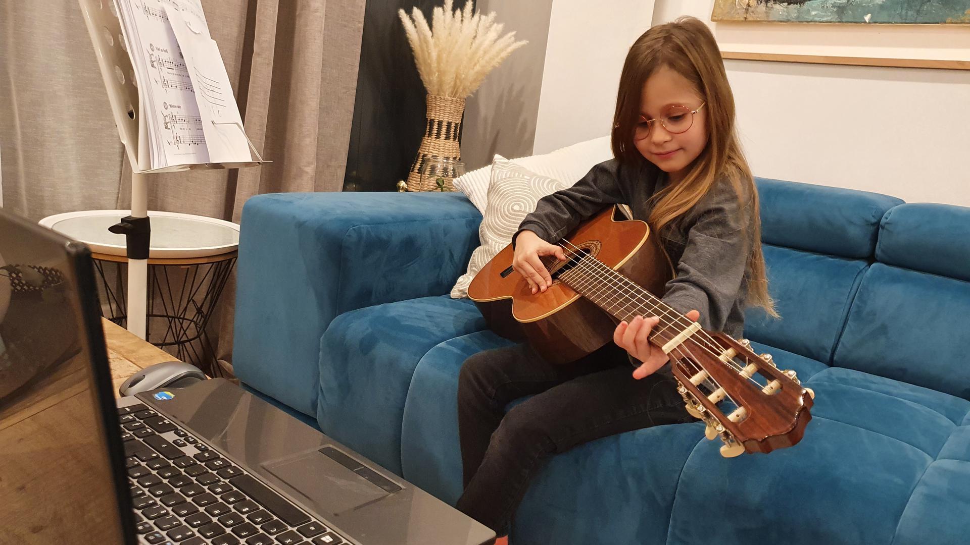 Ein Mädchen spielt Gitarre auf dem Sofa