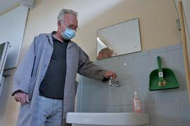 ein Hausmeister dreht einen Wasserhahn auf