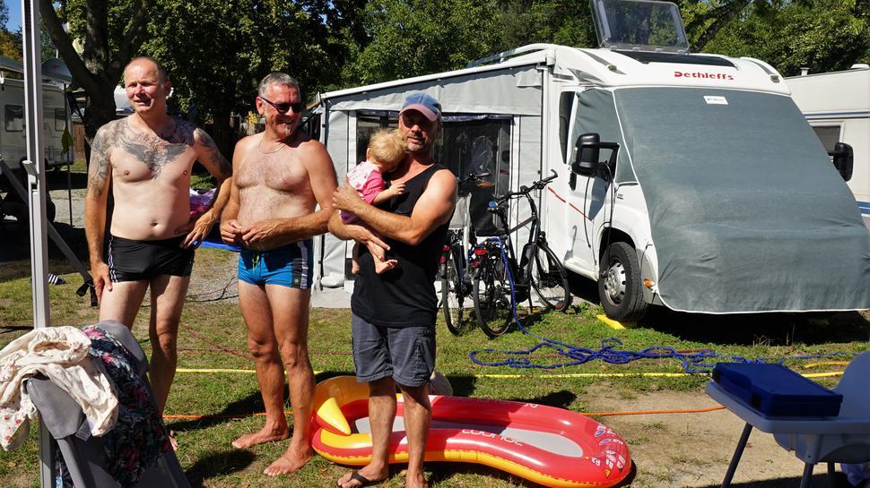 Drei Männer in Badehosen stehen auf einem Campingplatz.