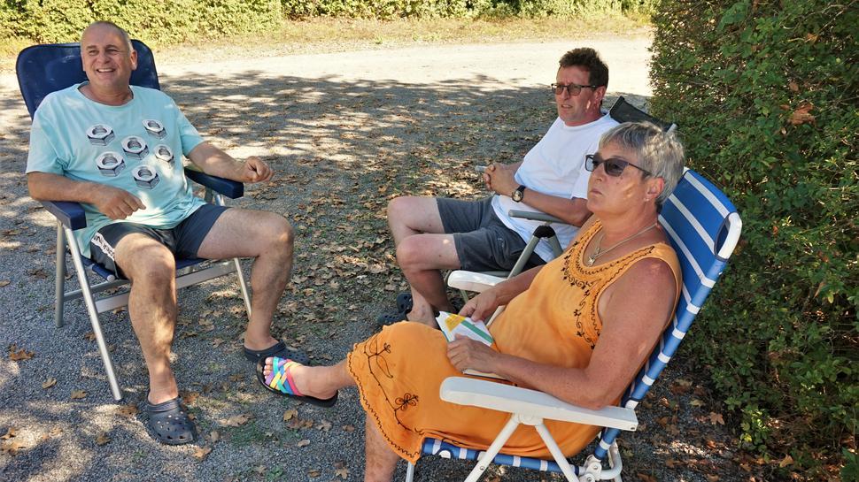Zwei Männer und eine Frau sitzen in Campingstühlen.