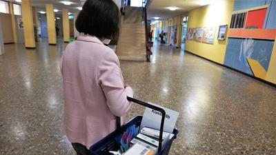 Eine Frau geht mit einem Korb durch die Pausenhalle.