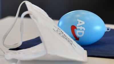 Eine FFP2-Maske und ein Osterei mit AfD-Konterfeit liegen auf einem Tisch.