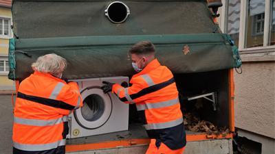 Zwei Männer von der Stadtreinigung laden eine alte Waschmaschine auf einen Lastwagen.