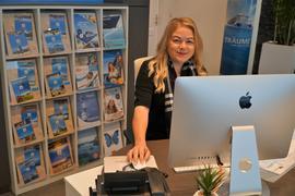 Selina Felsner sitzt vor ihrem Computer im Reisebüro.