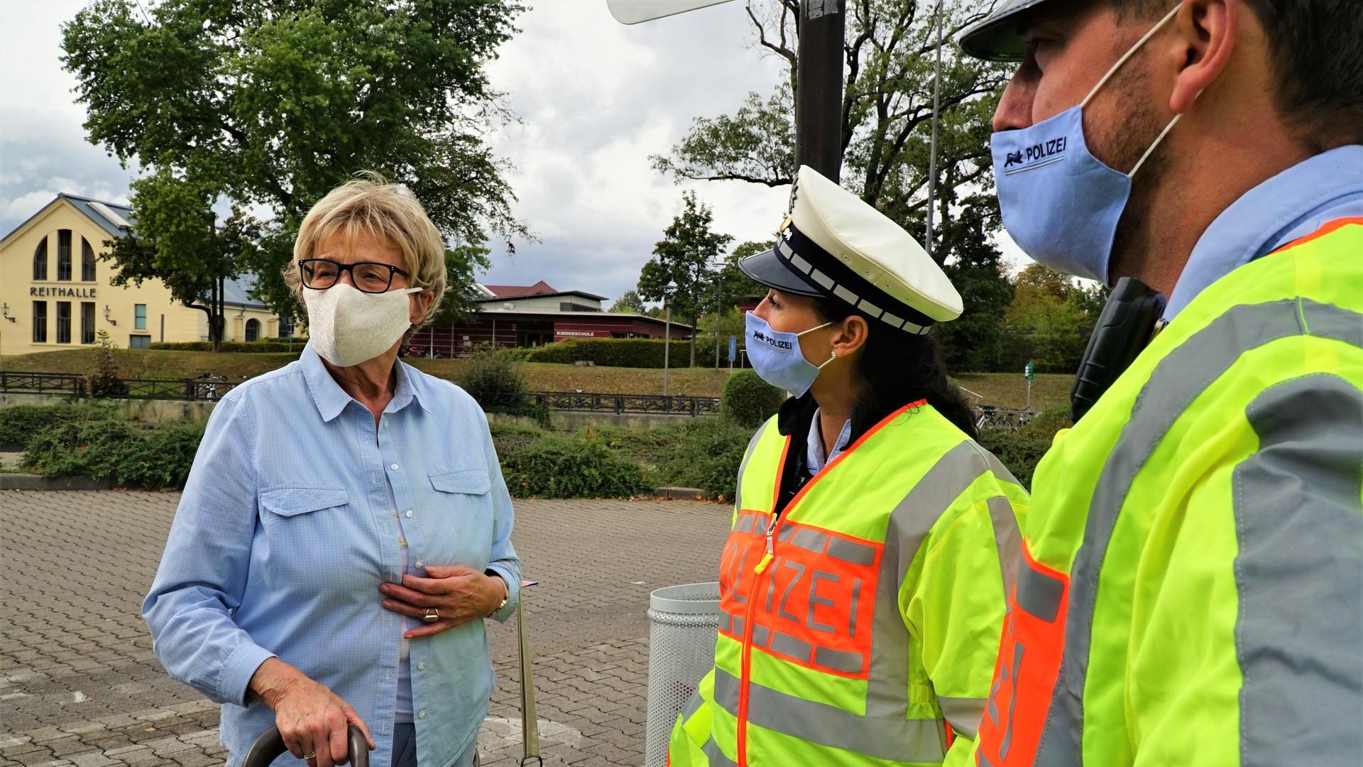 Zwei Polizisten mit Mundschutz im Gespräch mit einer Frau
