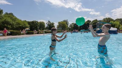Ein Mädchen und ein Junge spielen Ball in einem Schwimmbad.