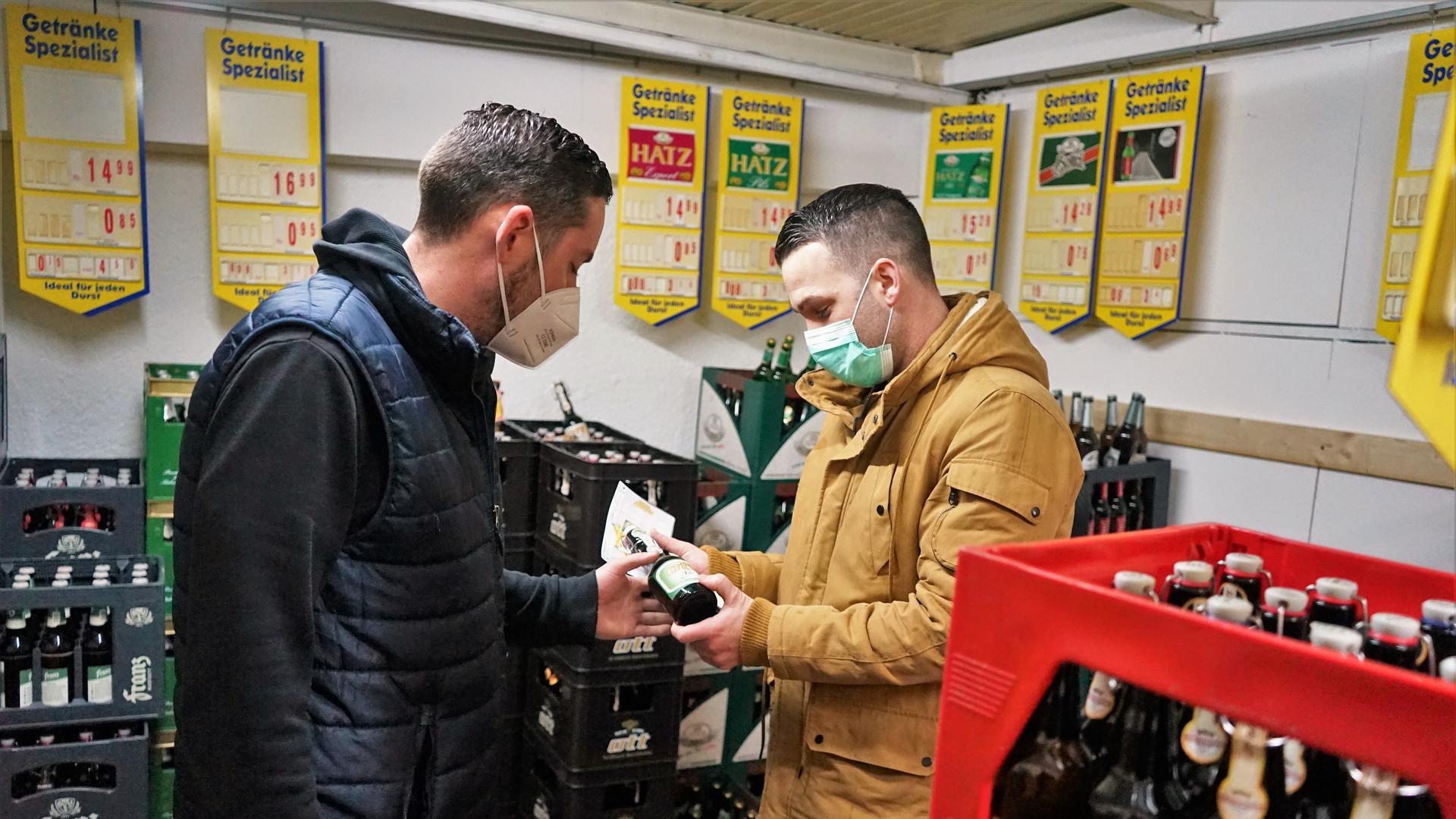 Zwei Männer mit Masken im Getränkemarkt