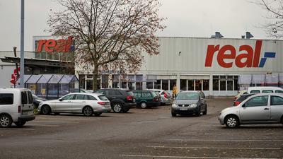 Ein graues Auto fährt auf dem Parkplatz der Rastatter Real-Filiale.