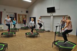 Sieben Frauen springen auf kleinen Trampolinen.