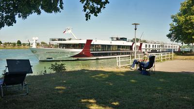Ein Fluss-Kreuzfahrtschiff liegt an einem Anleger vor Anker.