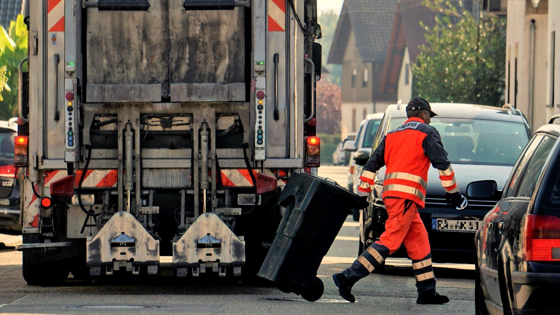 Ein Müllmann schiebt eine Tonne vom Lastwagen weg.