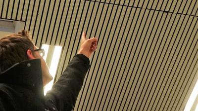 Ein Mann zeigt in einer Sporthalle auf ein Oberlicht.