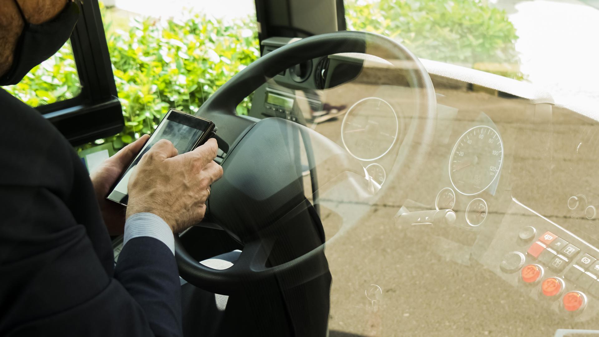 Hand mit Handy vor Buslenkrad