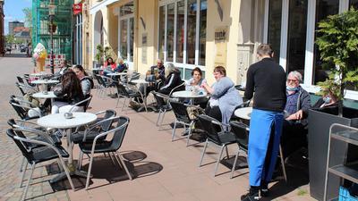 Vor dem Eiscafé Tutti Frutti in der Fußgängerzone in Rastatt sitzen nach Corona-Erleichterungen wieder erste Gäste.