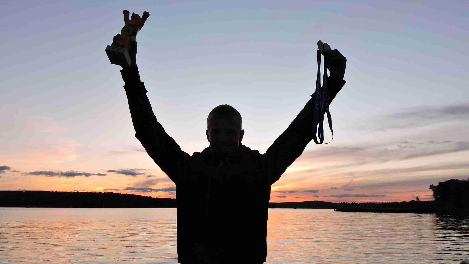 Riko Rockenbauch reckt seine Goldmedaille und ein Modell des Berliner Bären in die Höhe. Im Hintergrund geht die Sonne unter.