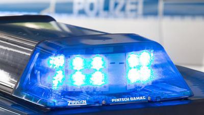 Ein Blaulicht leuchtet auf dem Dach eines Polizeiwagens. Im Hintergrund steht ein weiterer Streifenwagen.