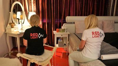 Zwei Damen sitzen mit dem Rücken zum Betrachter auf einem Hocker und auf einem Doppelbett. Sie tragen T-Shirts mit der Aufschrift Redlight on.