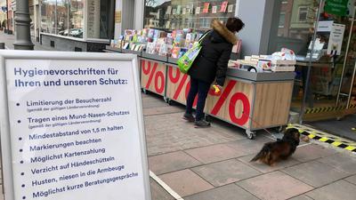 Eine Frau steht vor einer Buchhandlung und hat einen Hund an der Leine